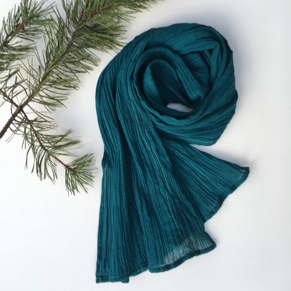 teal blue gauzy organic cotton scarf displayed on table with pine sprig