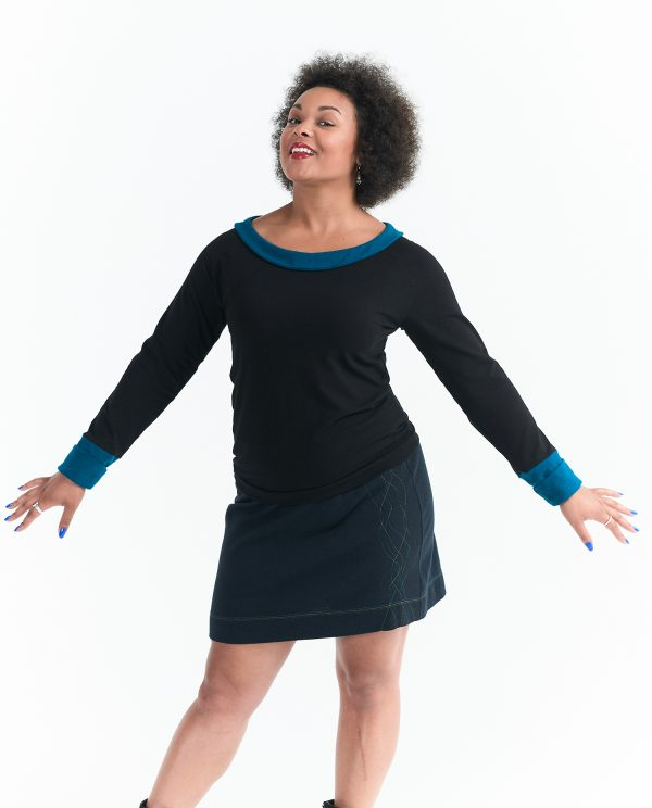 long sleeve black top with blue collar and long blue cuffs on happy black model wearing