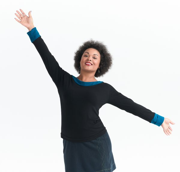 vibrant black model with arms wide and a smile wearing long sleeve organic cotton holiday top in black with blue trim