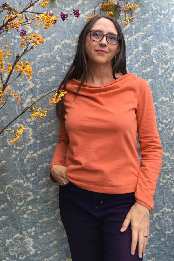 cowl neck long sleeve top in a soft orange on lady with long brown hair and berries in background