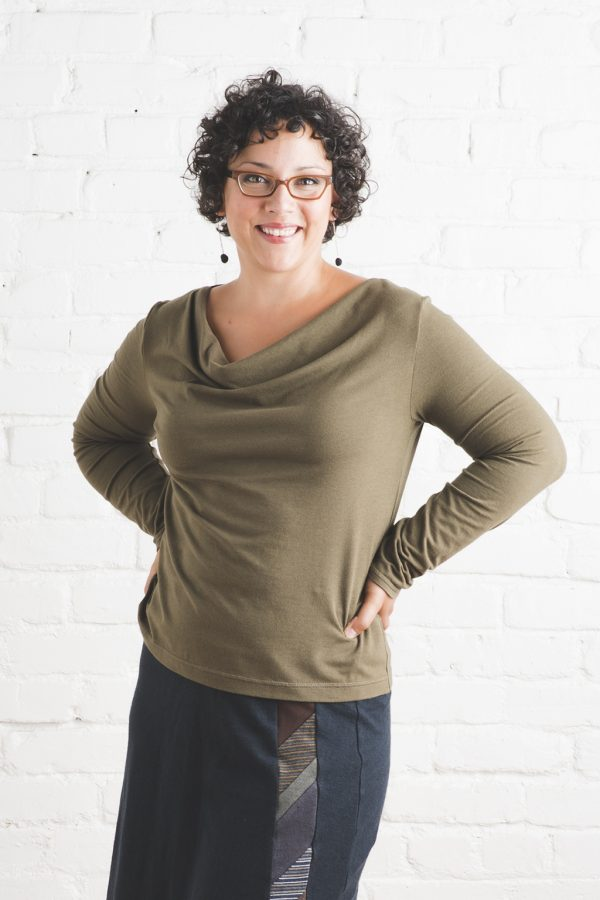 woman with dark curly hair and glasses wearing cowl neck, long sleeve, soft top in caper green