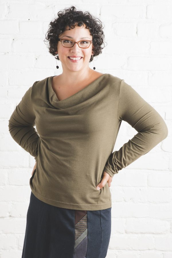 caper green cowl neck long sleeve top on lady with curly dark hair and glasses