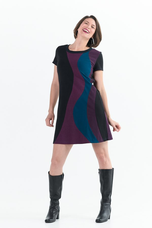 Vivid Element | Solar Flare Dress shown in swirls of berry. The length is just above the knee, it has short sleeves and is on lady with black boots