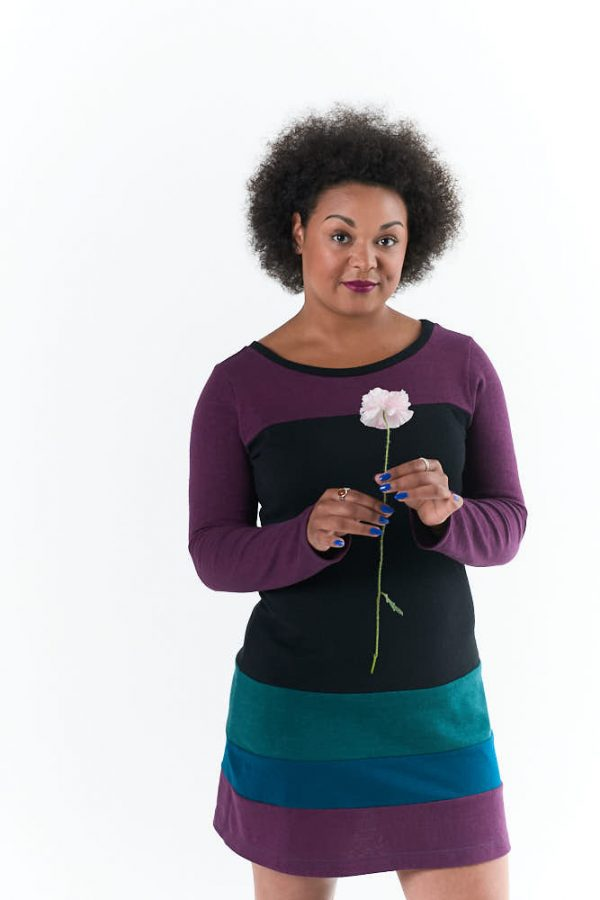 black model holding a poppy and wearing a long sleeve dress with black bodice, sleeves in huckleberry and stripes at the hem in blueberry, huckleberry and juniper berry colors.