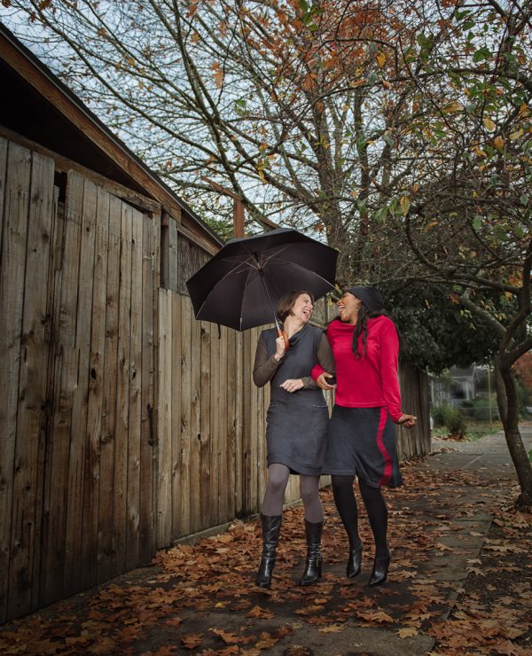 ladies wearing sustainable fashion and skipping in the rain