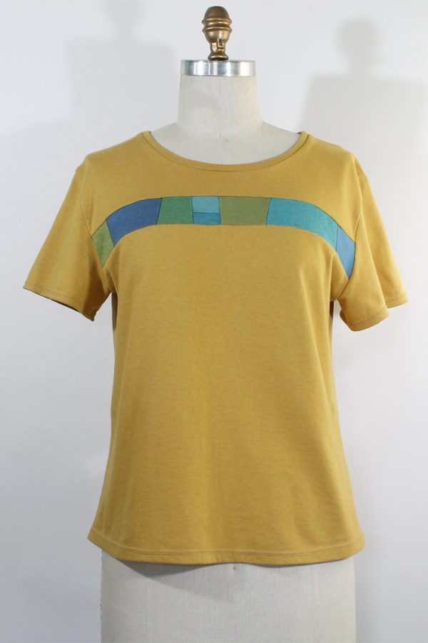 golden yellow top with short sleeves and a strip of collaged fabrics in blues and greens across the front in a slight curve.