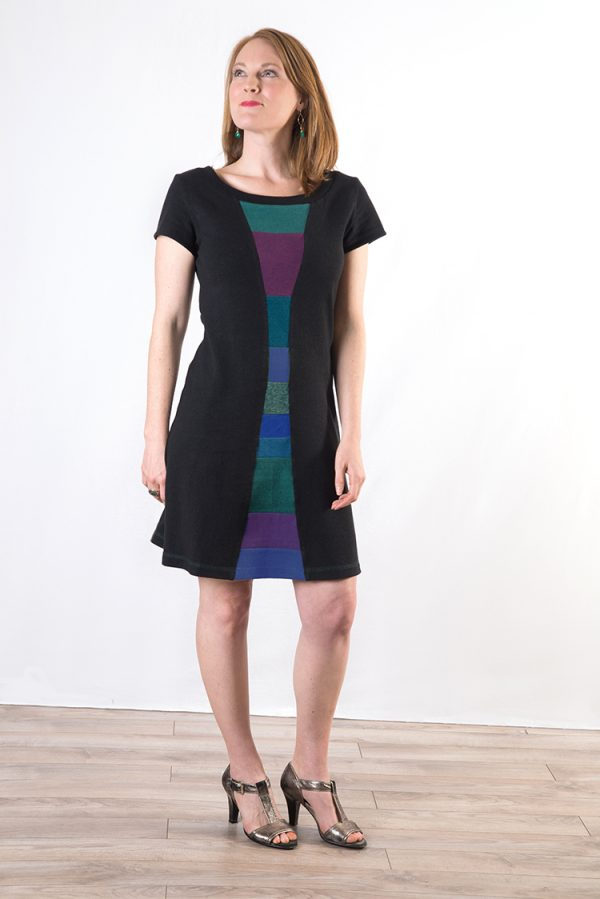 knee length black dress on a lady with red hair, dress has a multi colored collage down the front
