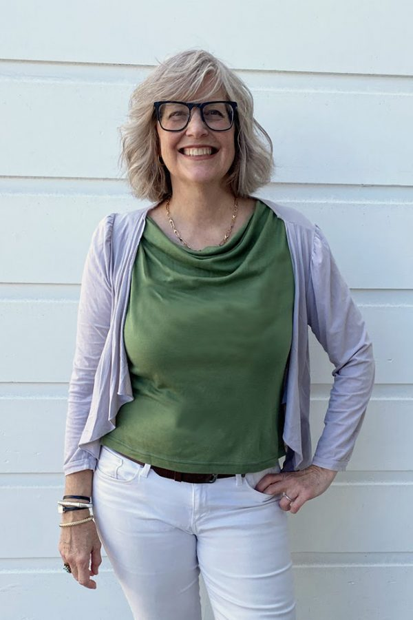 Mary in Vivid Element's soft drapey cowl neck sleeveless Saturn Top in sage green with a big smile and white pants