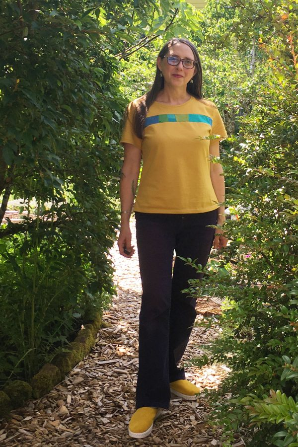 Amy wearing yellow mineral tee with yellow shoes, purple pants outside in garden