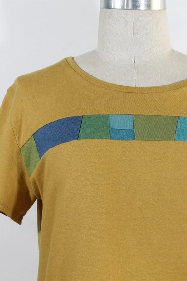 closeup of organic cotton tee in yellow with blue and green trim