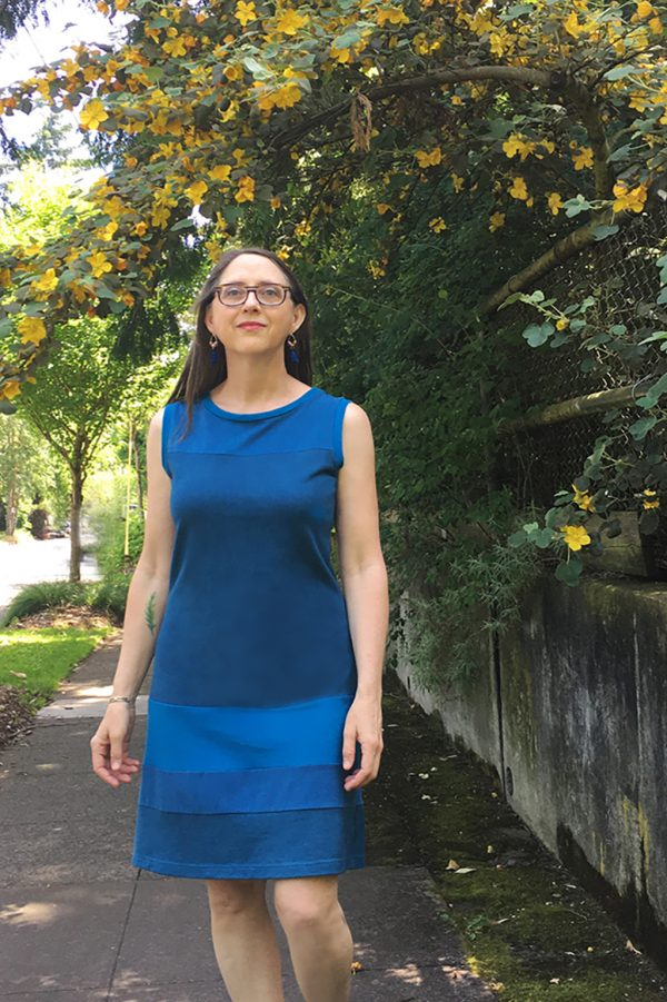 sleeveless blue poppy dress in front of yellow flowers