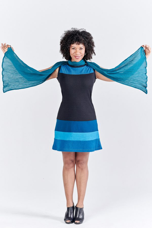 black model in blue and black hemp dress. she is holding one end of a scarf in each hand, making angel wings in a way.