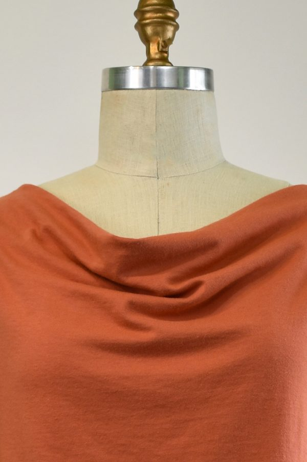 close up of folds of cowl neck top on dress form in soft ginger orange organic cotton jersey