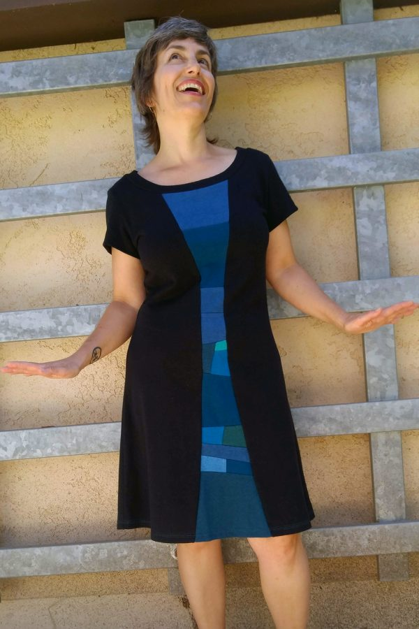 Woman with short hair wearing the short sleeve black time travel dress. The hemp dress has a blue collage down the center front.