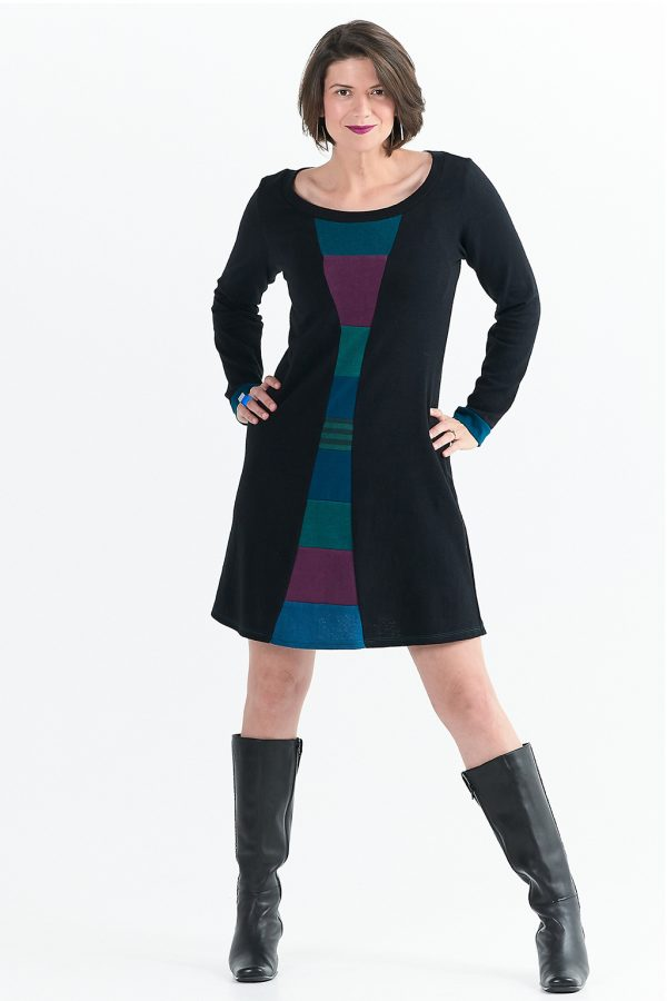 black hemp dress with long sleeves and zero waste collage down the center front. it is modeled by a tall lady with boots and hands on her hips.