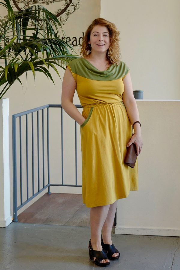 pretty lady in yellow and green wildflower dress with cowl neck, pockets, and colorblocking of organic fabrics