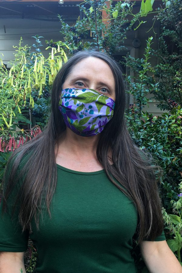 lady wearing purple and green floral face mask out in garden