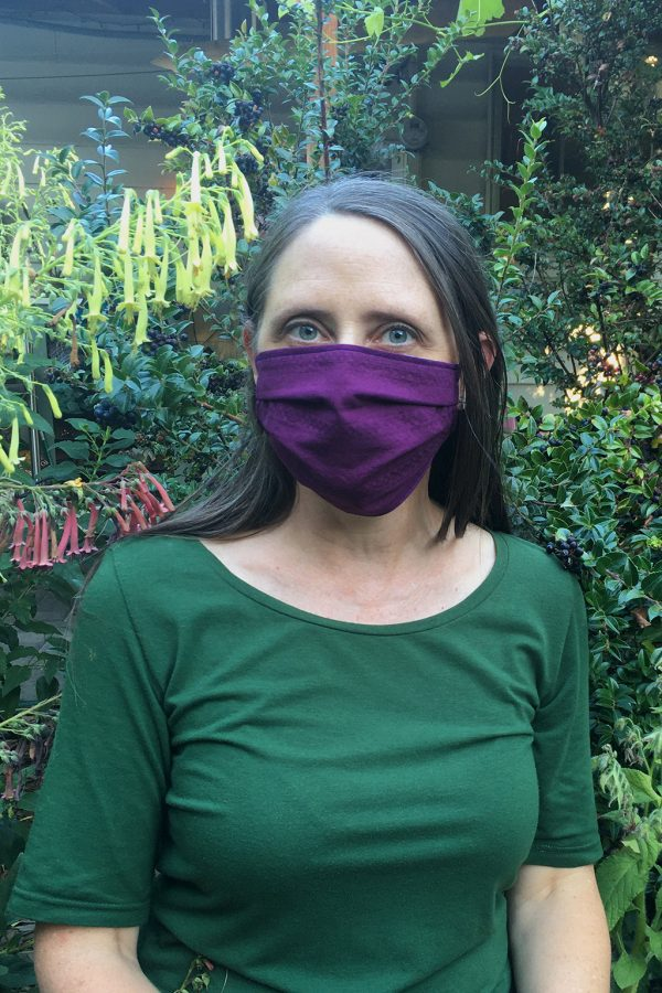 Huckleberry colored cloth organic cotton facemask on woman in garden with flowers and huckleberries in background