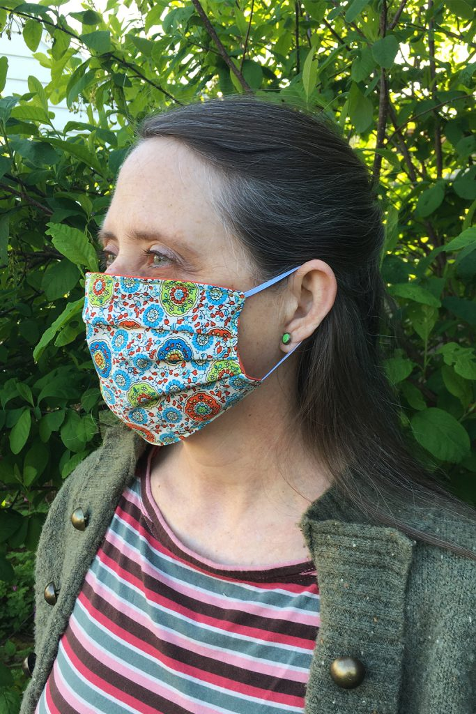 woman with face mask side view. mask is a fun colorful printed quilters cotton background of photo is osoberry leaves