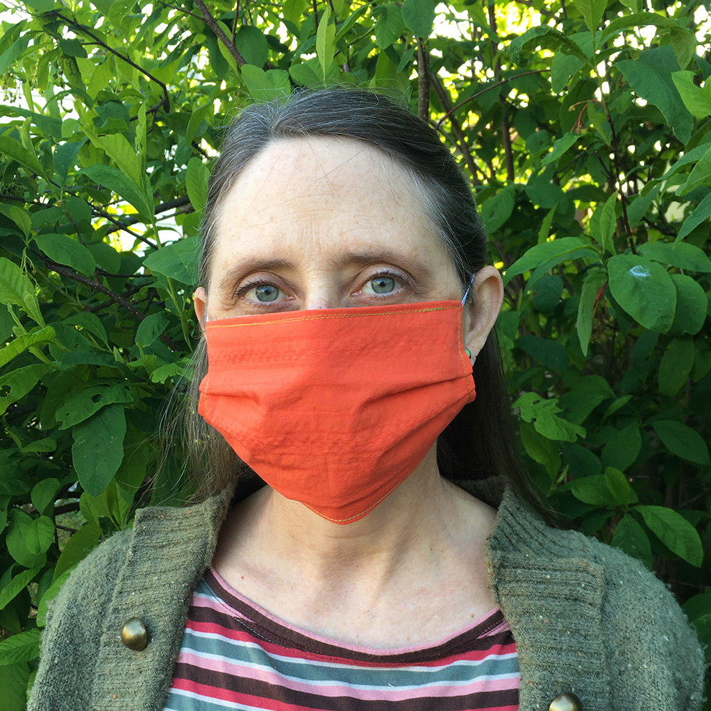 woman wearing organic cotton orange poppy facemask with blue eyes and Indian plum leaves behind her. mask has elastic straps over the ears.