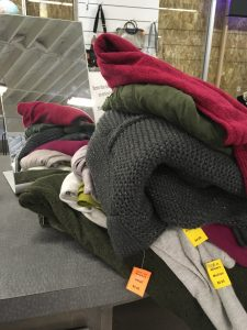 pile of second hand clothing with tags