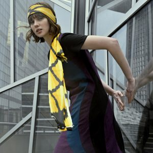 woman in Vivid Element solar flare dress with waves of purple and blue and yellow scarf leaninng on a building in Paris
