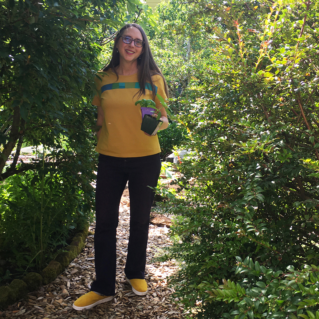 Amy with yellow Mineral Top and yellow Bendy shoes, holding plants in her garden