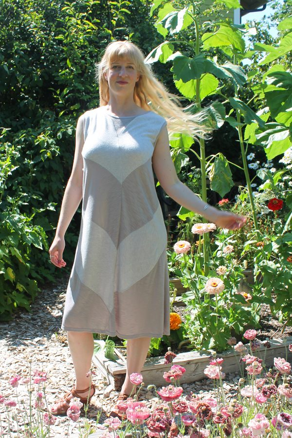 flowy offwhite and soft pink dress on model with blonde hair in garden