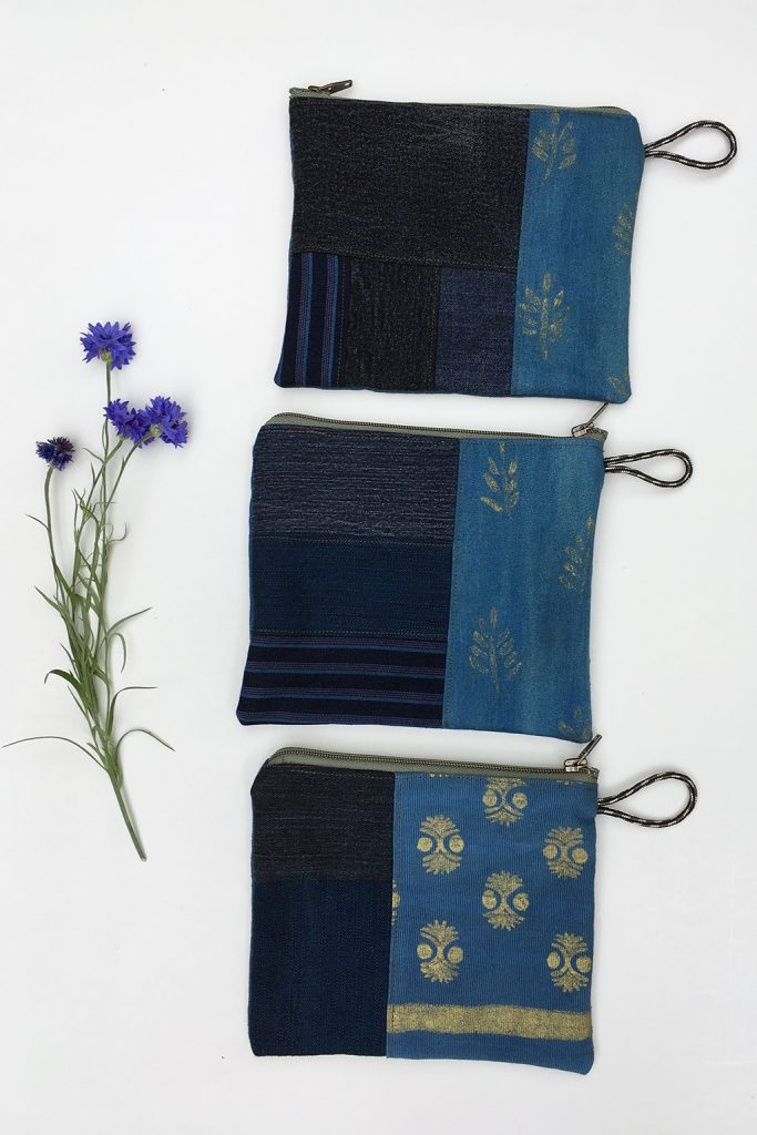 three blue denim zippered pouches