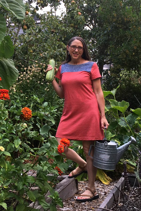 designer in orange and blue dress out in the garden, holding a zucchini and watering can.