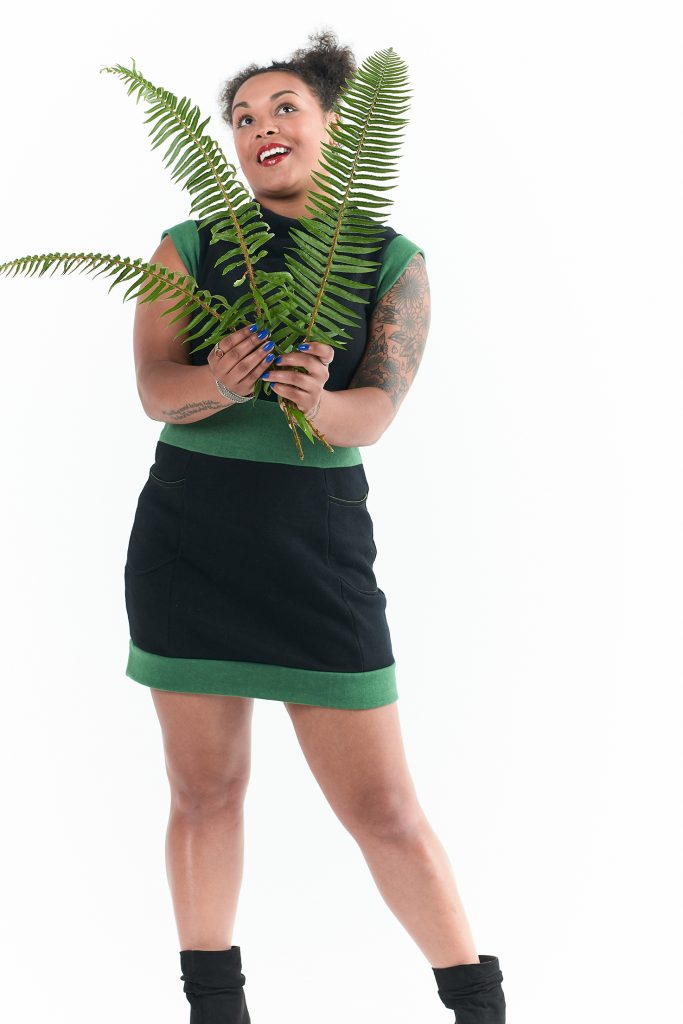 woman in black and green hemp dress with 3 sword fern leaves