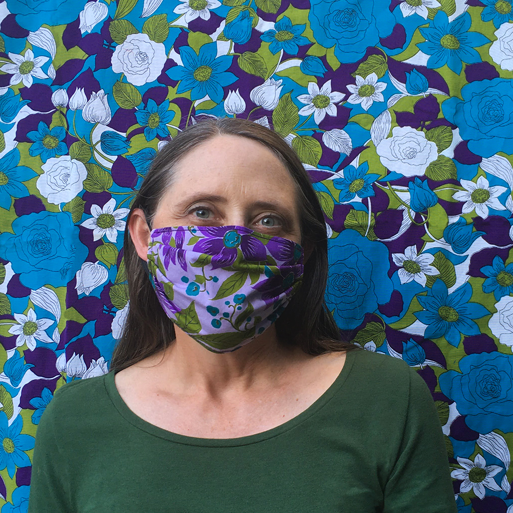 woman in floral fabric facemask with floral fabric background