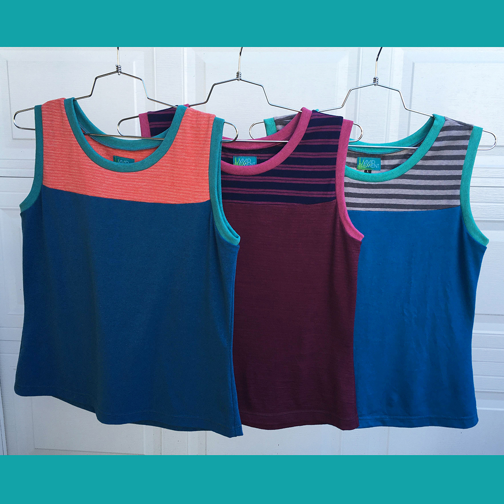three bright tank tops on hangers in blues, orange, stripes and huckleberry