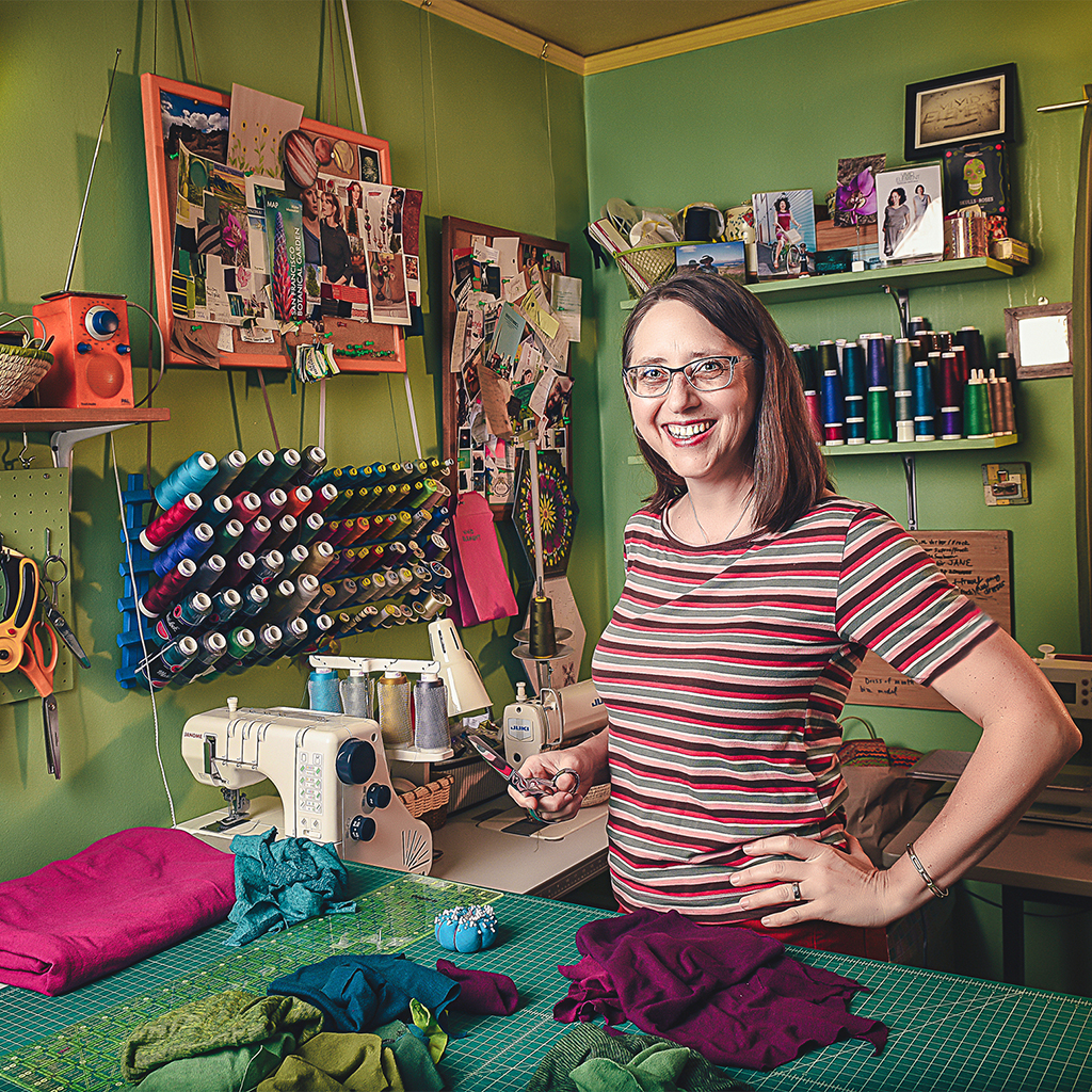 artist Amy Daileda in her studio with green walls, scissors, fabric, sewing machines and thread.