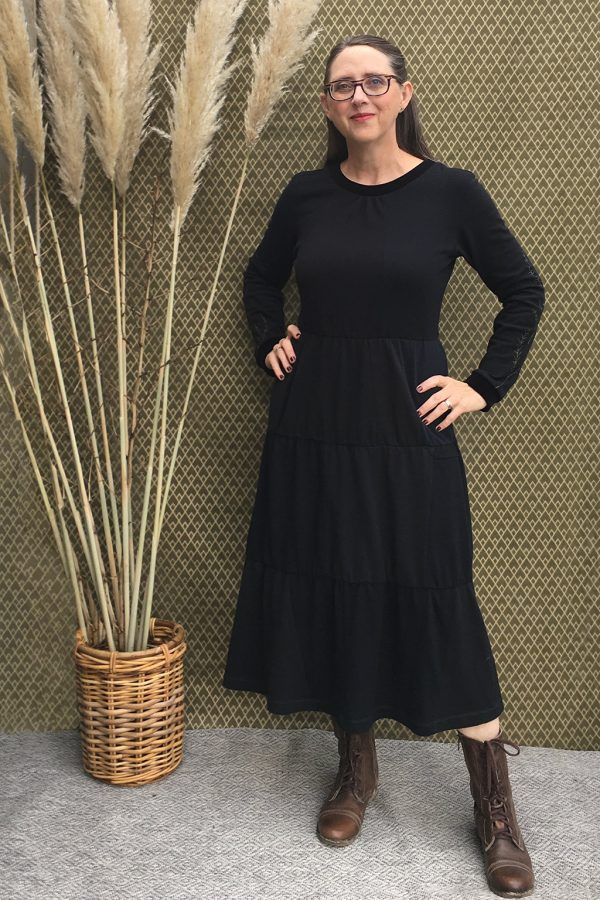 long sleeve, long black dress with elastic waist, tucks at neck, pockets and 3 gathered tiers. Modeled by designer in boots with tall grasses in background.