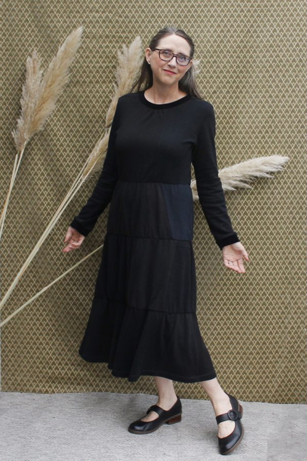 long black dress with long sleeves on lady with glasses. Mid-calf length, gathered waist and 2 more gathers on skirt.