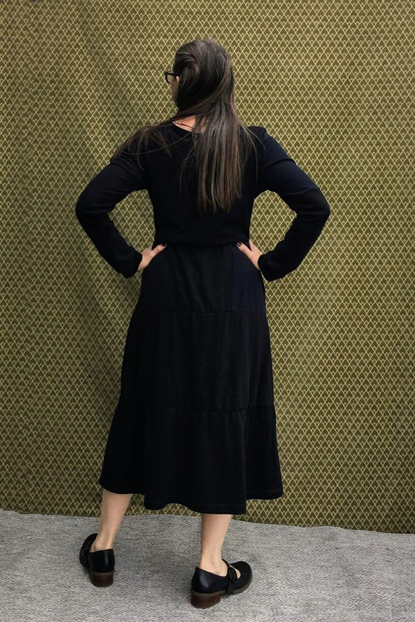 model showing back of long black dress with gathered waist.
