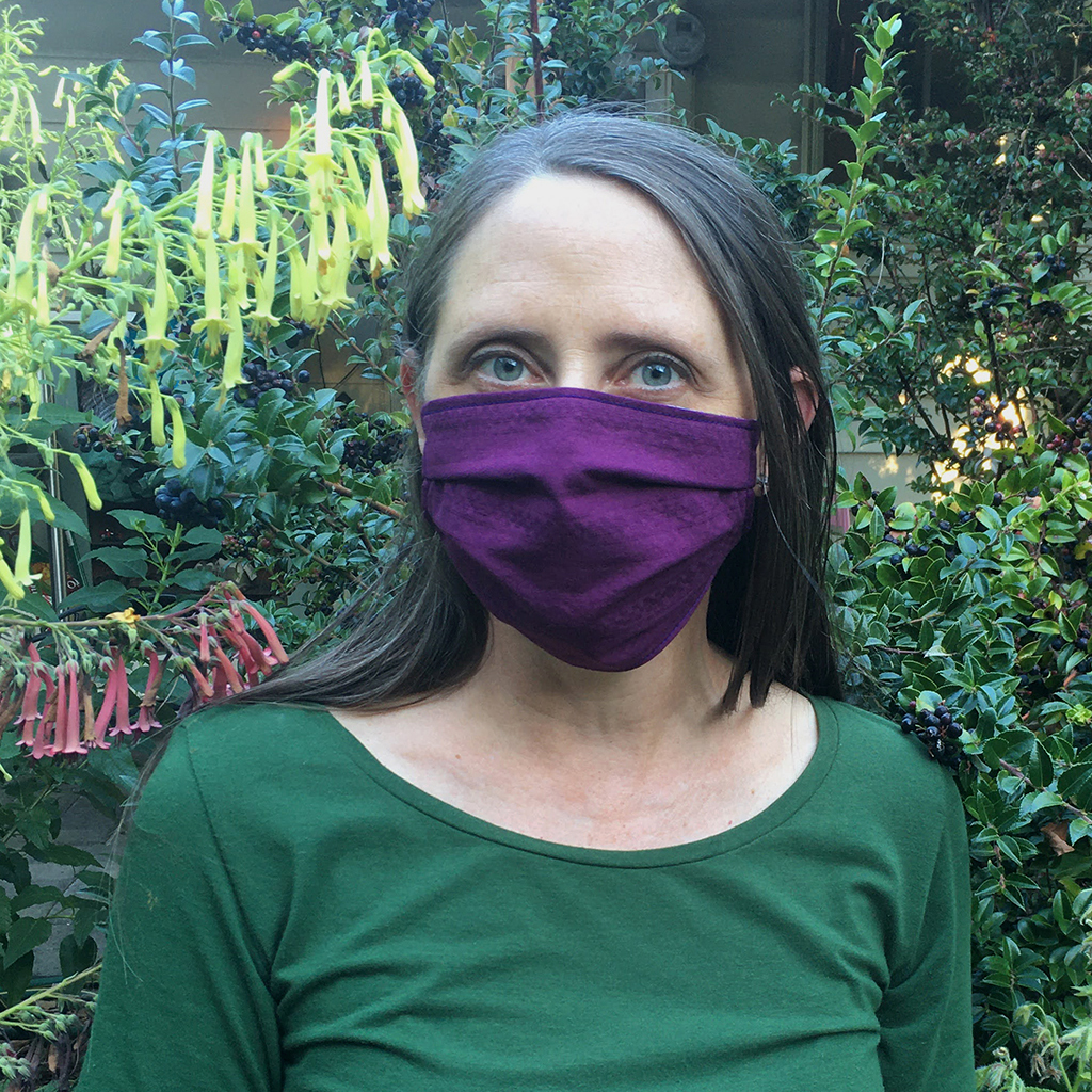 designer in garden with yellow flowers and huckleberries wearing huckleberry colored cloth face mask