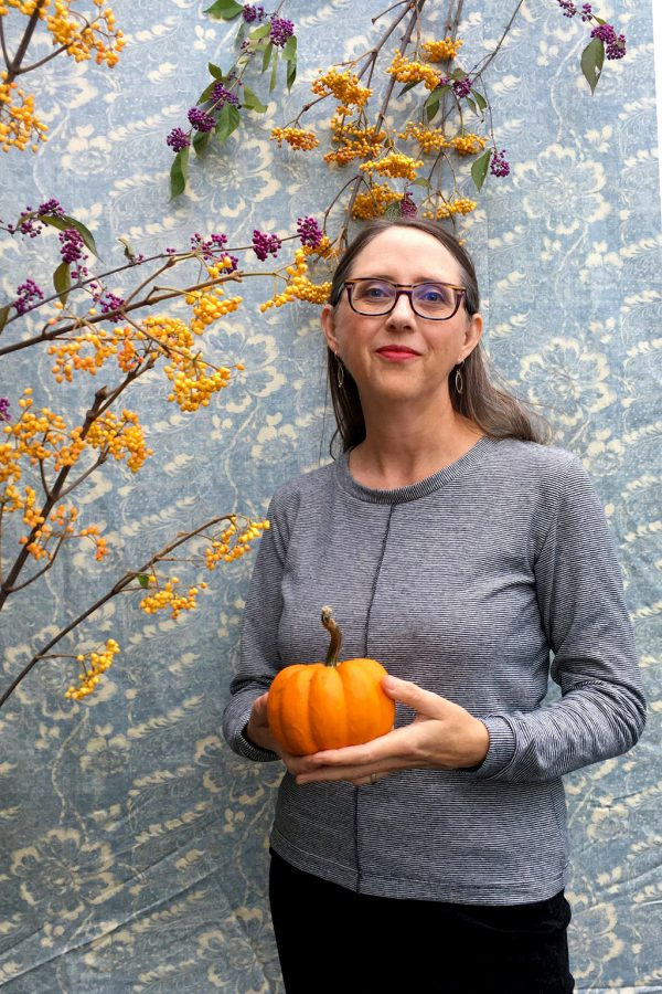 Lady with brown hair wearing a long sleeve top made out of tiny black and white stripe fabric. The center front has visible seam stitching. She is holding a pumpkin.