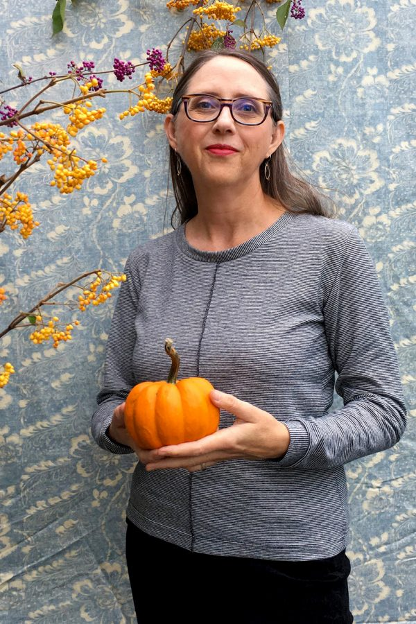 lady with pumpkin wearing long sleeve hemp top that is made from tiny black and white striped fabric. the center front seam stitching is visible.