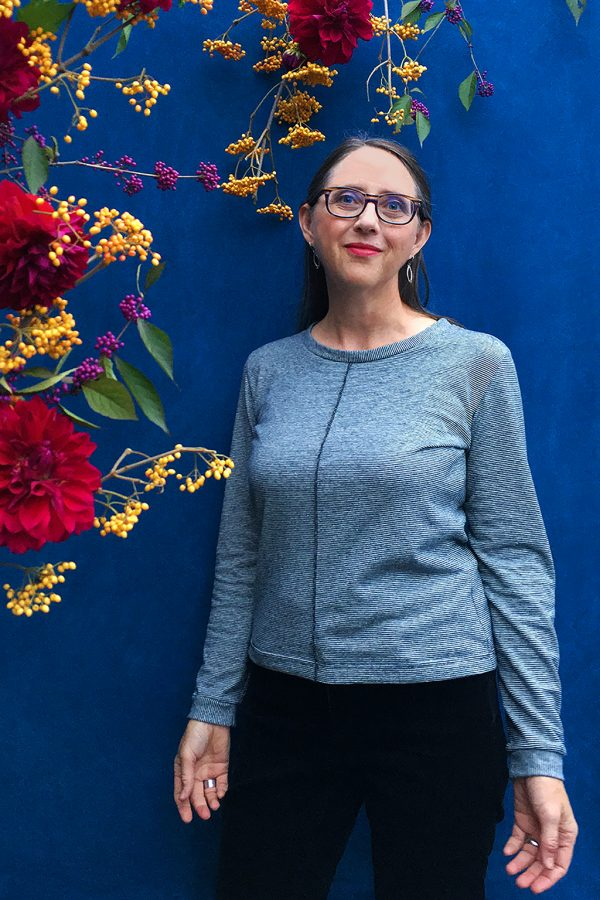 Designer wearing long sleeve hemp top with tiny black and white stripes and seam down center front. Blue backround with live red, pink and yellow flowers and berries.