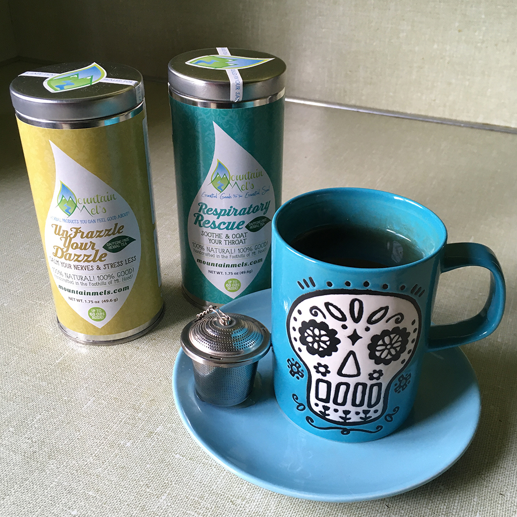 Mountain Mel's tea in tin containers: Unfrazzle Your Dazzle and Respiratory Rescue, a handmade mug with a flowery skull and a tea strainer