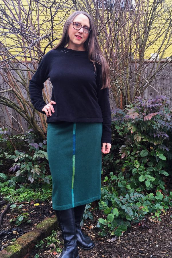 Designer in fall garden with below knee length dark green skirt, black boots and black sweatshirt.