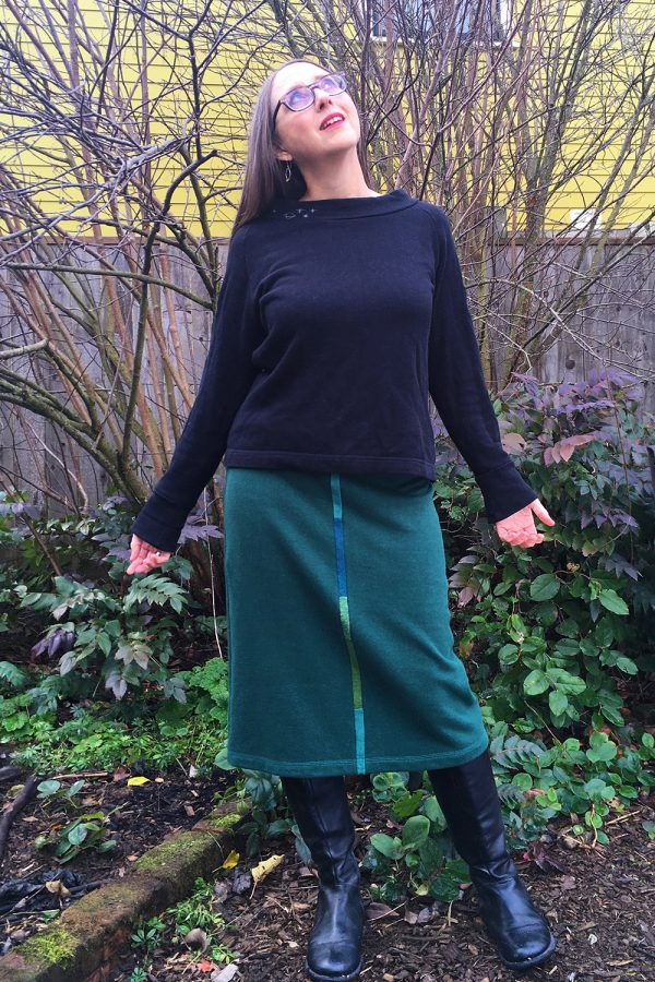 green skirt on Portland designer. In fall oregon native plant garden with salal, oregon grape and oso berry in background.