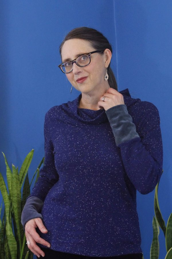 slow fashion designer with glasses wearing cozy looking dark blue long sleeve top, showing velour cuff.