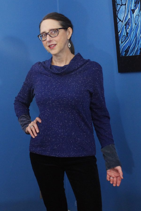 slow fashion designer wearing long sleeve blue hemp top with blue background.