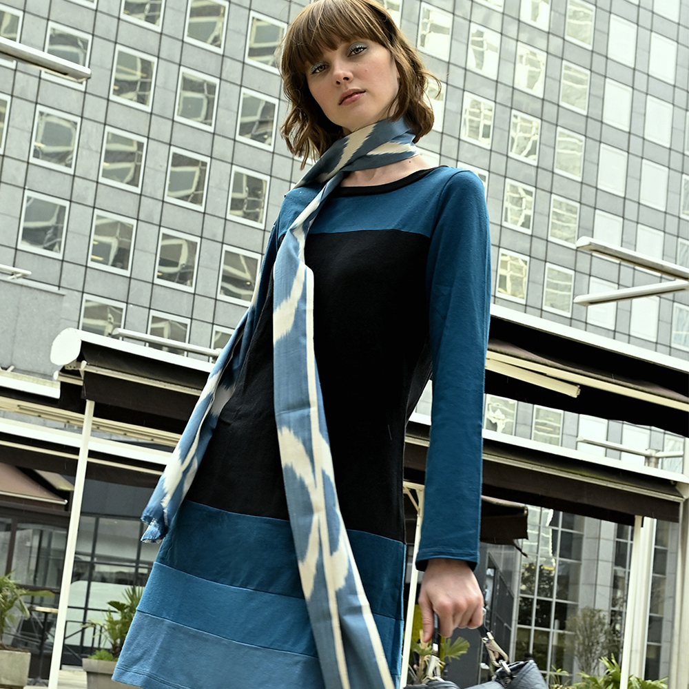 long sleeve hemp dress in black with color block sections in blues on woman in Paris with long scarf and blue eyeshadow