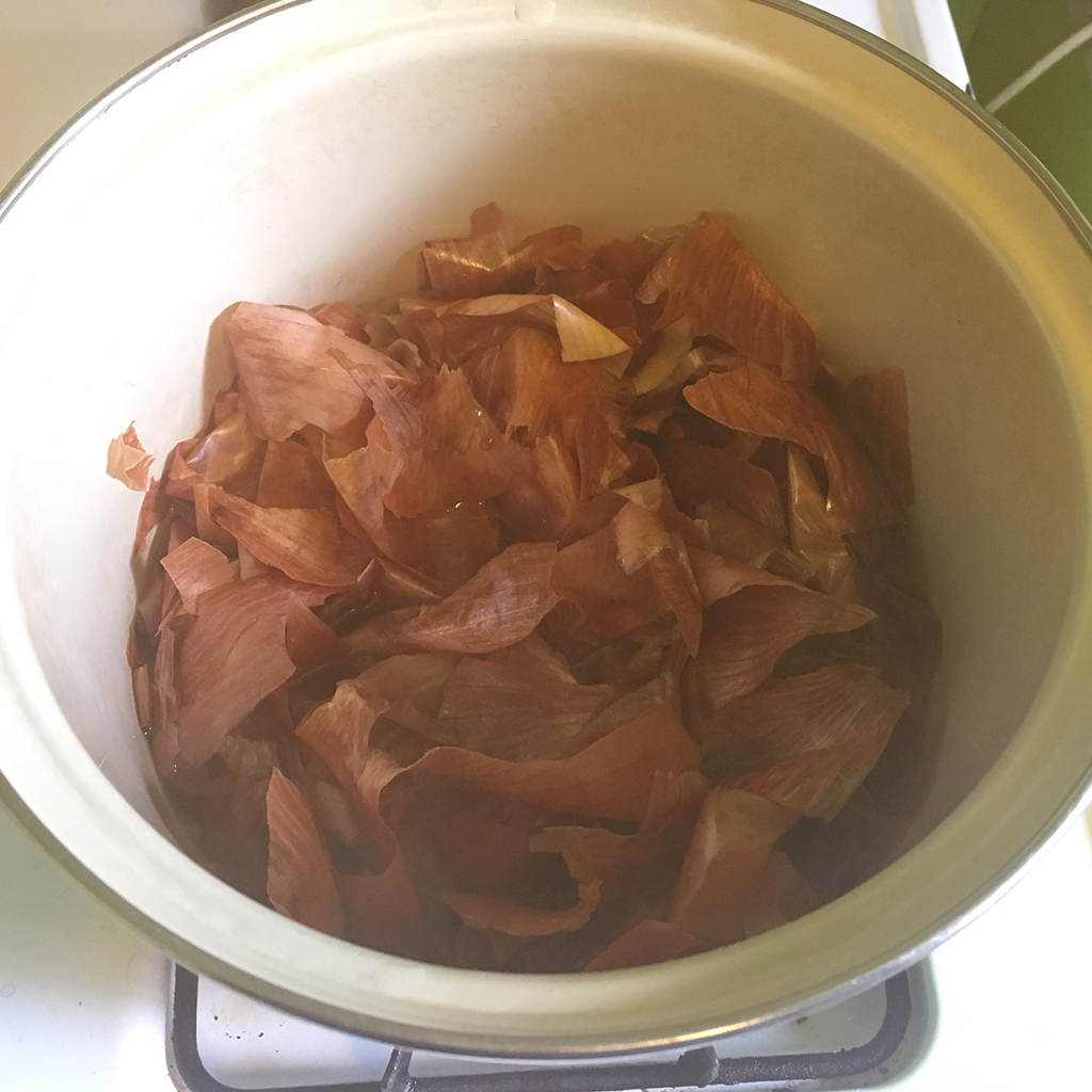yellow onion skins cooking in pot for natural egg dye