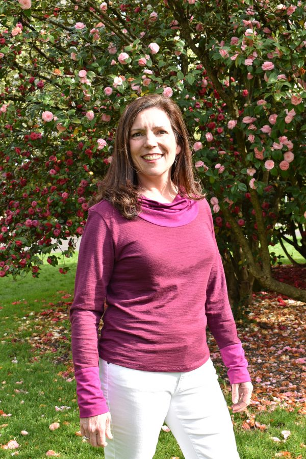 smiling model in long sleeve hemp huckleberry top with pink camelias in the background