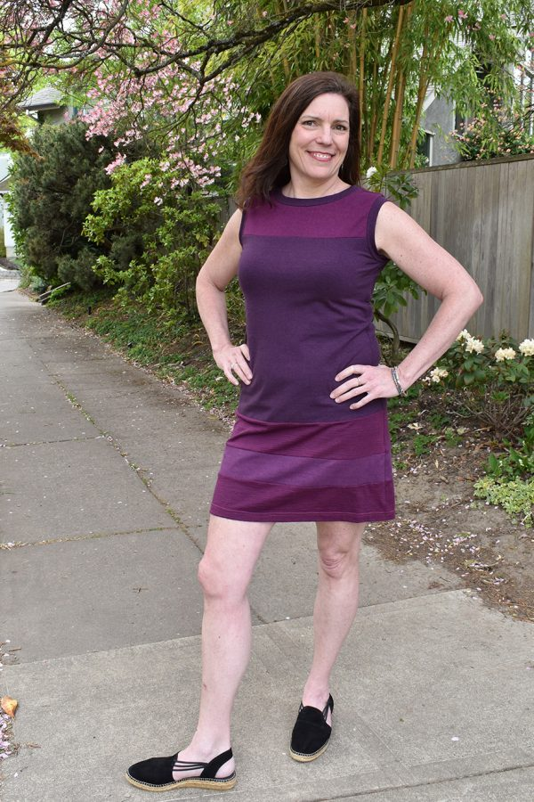 sleeveless purple and berry striped dress, above the knee, 60s style, on smiling lady with brown hair and black shoes. She's under a pink flowering dogwood tree.